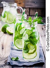 Detox water with cucumber, lime and mint in bottles