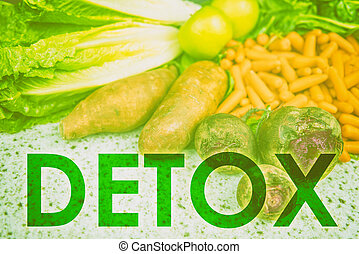 DETOX word title written across uncooked raw vegetables background for eating healthy diet weight loss concept. Green filter over farmer's market produce for health food concept