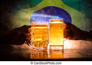 deux amis, grillage, (clinking), à, lunettes, lumière, bière, à, les, pub., beau, fond, à, vue brouillée, de, drapeau, de, brazil., soutien, ton, pays, à, bière, concept.