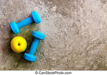 deux, bleu, poids, dumbbells, et, jaune, pomme, sur, béton, arrière-plan.