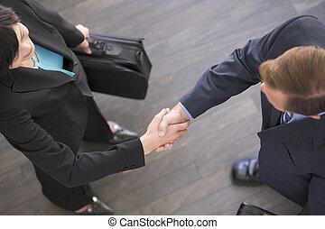 deux, businesspeople, debout, intérieur, serrer main