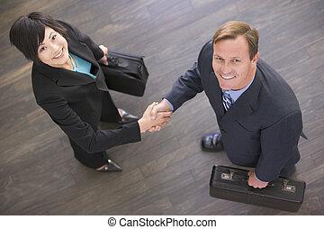 deux, businesspeople, intérieur, serrer main, sourire