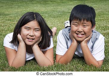 deux enfants, pose, dans, les, herbe