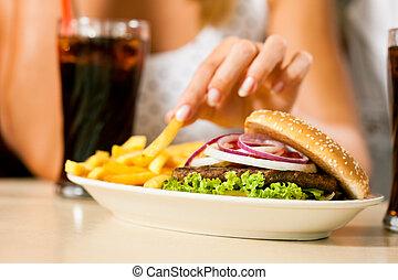 deux femmes, manger, hamburger, et, boire, soude