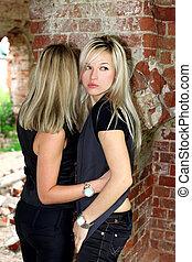 deux filles, à, vieux, mur brique