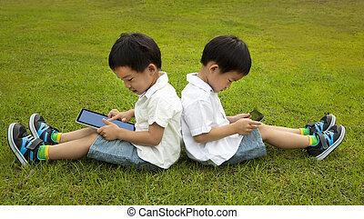 deux, gosses, utilisation, touchscreen, pc tablette, herbe