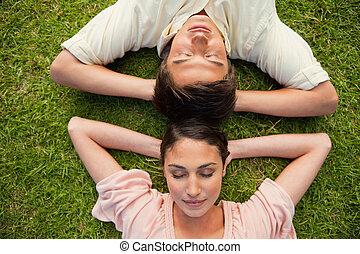 deux, gros plan, femme, cou, reposer, tête, bras, leur, derrière, fermé, herbe, yeux, mensonge, homme