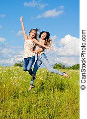 deux, heureux, jeunes femmes, sauter