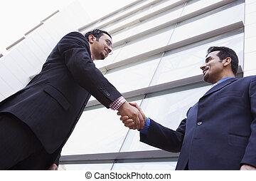 deux hommes affaires serrant main, dehors, bâtiment bureau