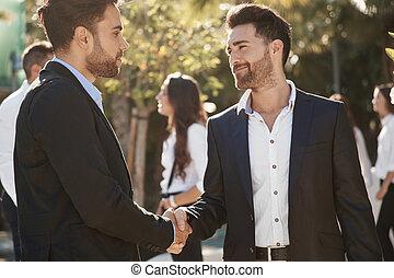 deux hommes affaires serrant main, dehors