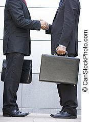 deux, hommes affaires, tenue, serviettes, dehors, serrer main