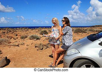 deux, jeunes femmes, à, voiture, regarder, carte route, sur, a, plage, contre, mer, et, ciel