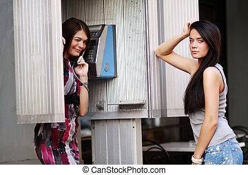 deux, jeunes femmes, conversation, sur, payphone