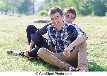 deux, jeunes hommes, reposer ensemble, sur, herbe verte