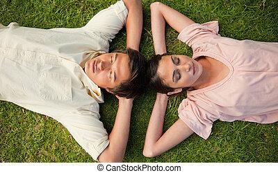 deux, yeux, femme, cou, reposer, tête, bras, leur, derrière, fermé, herbe, mensonge, homme