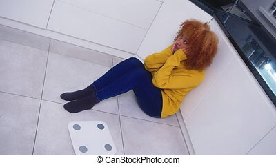 Devastated young african american black woman sitting on the flor with weight scale in front. Weight loss and mental health concept. High quality 4k footage