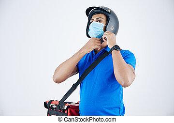 Develiry man putting on helmet
