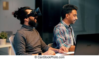 developers with virtual reality headset at office -...