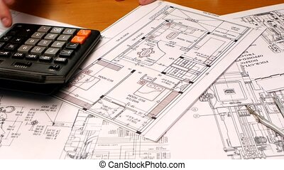 Developing engineering project. Male architect checking numbers on blueprint during house construction planing.