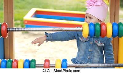 Child girl plays in the playground and learns to count in the game. Entertainment for children.