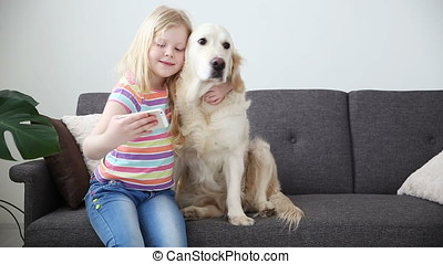 devices in the lives of children. A little girl does selfie with her dog on a smartphone. Location - sofa in the living room.