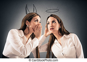 Devil speaks to angel - Girl with devil horns speaks to a...