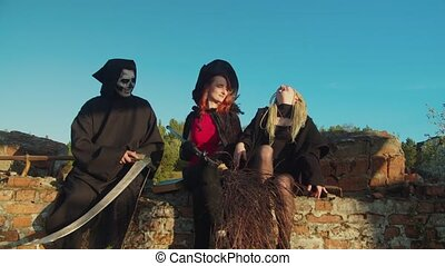 Spooky death reaper with scythe, black witch with broom and female vampire communicating , plotting evil deeds on halloween holiday while devilry gathering for witch sabbath at sunset.