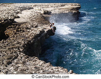 Devils Bridge with tourist at Indian Town Point National Park on Antigua Barbuda in the Caribbean Lesser Antilles West Indies.