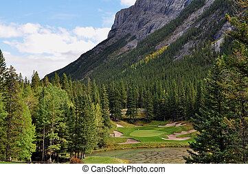 A Rocky Mountain par 3 with bunkers and a front pond, with mountain in background