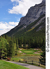 A Rocky Mountain golf course par 3 with a pond in front and mountains in the background