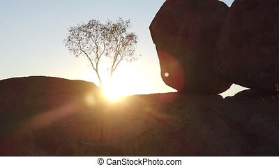 SLOW MOTION: Australia, Northern Territory. Aboriginal land in Red Centre. Sunbeams of sunset behind iconic the Eggs of mythical Rainbow Serpent at Karlu Karlu - Devils Marbles Reserve.