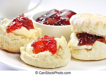 Home-baked scones with strawberry jam and clotted cream, served with a cup of tea. Known as a Devonshire tea. Focus on front scone.