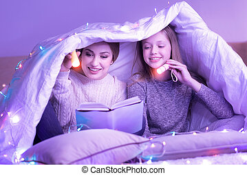 Devoted mom and daughter reading under the blanket