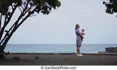 Devoted mother and baby cuddling, spending bonding quality time observing bright blue cloudscape. Attentive parenting and family lifestyle concept. Nature and people background.