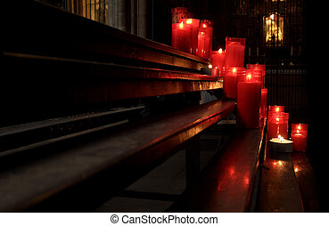 Devotional candles flaming in the dark of an spanish church