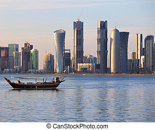 Dhow and Doha skyline - A dhow returns to harbour in Doha,...