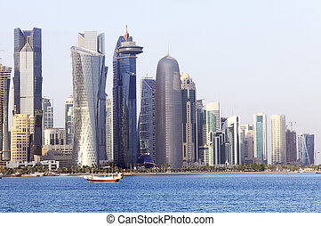 Dhow and doha towers - A dhow passes beneath some of the...