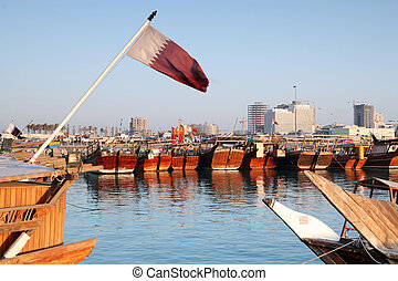 Dhow harbour and flag - The dhow harbour in Doha, Qatar,...