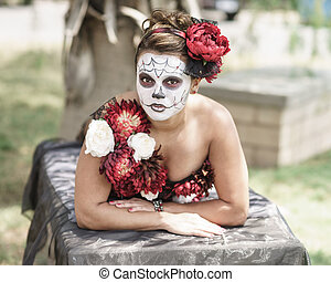 Female wearing Day of The Dead (Dia de los Muertos) make up and traditional costume