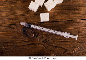 Diabetes is terrible disease. A lot of sugar cubes with syringe