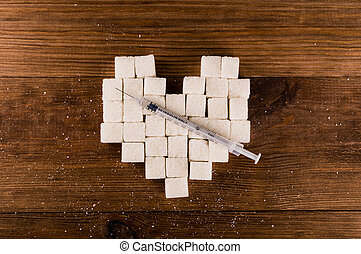 Diabetes is terrible disease. Heart of sugar cubes with syringe