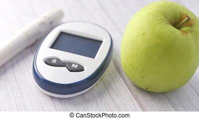 diabetic measurement tools, apple on table .