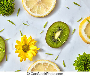 Diagonally floral patter from spring flowers, kiwi, lemon slices. Top view of flowers background.