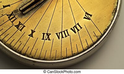 Dial of a sundial spinning on a white background. Close up -...