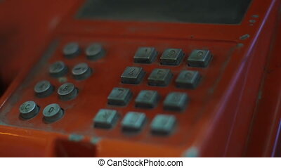 Dialing number on public phone in booth close-up