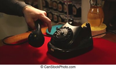Dialing with an retro rotary phone, man in the office dials the old phone