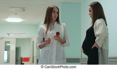 Dialogue between a pregnant woman and a female doctor in the corridor of the hospital.