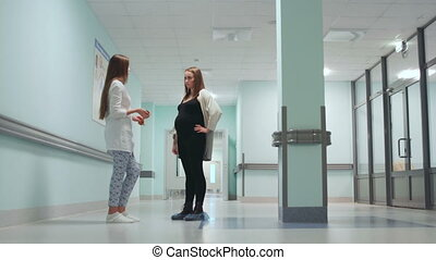Dialogue between a pregnant woman and a female doctor in the corridor of the hospital. Preparation for childbirth. Consultation on childbirth. Smiling people