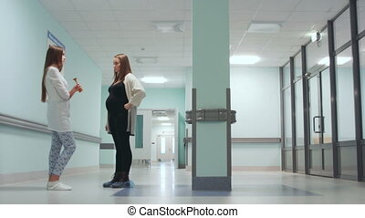 Dialogue between a pregnant woman and a female doctor in the corridor of the hospital. Preparation for childbirth. Maternity consultation.