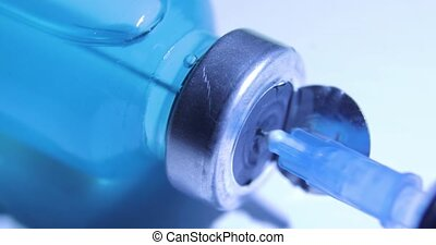 Dialsof drugs for vaccine injection with needle and syringe on blue background, closeup view. Coronavirus vaccination concept, COVID-19. Needle and blue vaccine bottle at hospital. Pandemic concept.